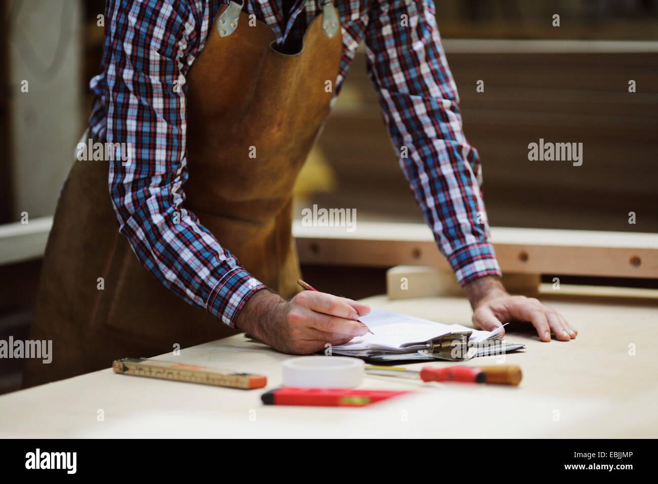 Cropped shot of mature craftsman making notes in organ workshop - Stock Image