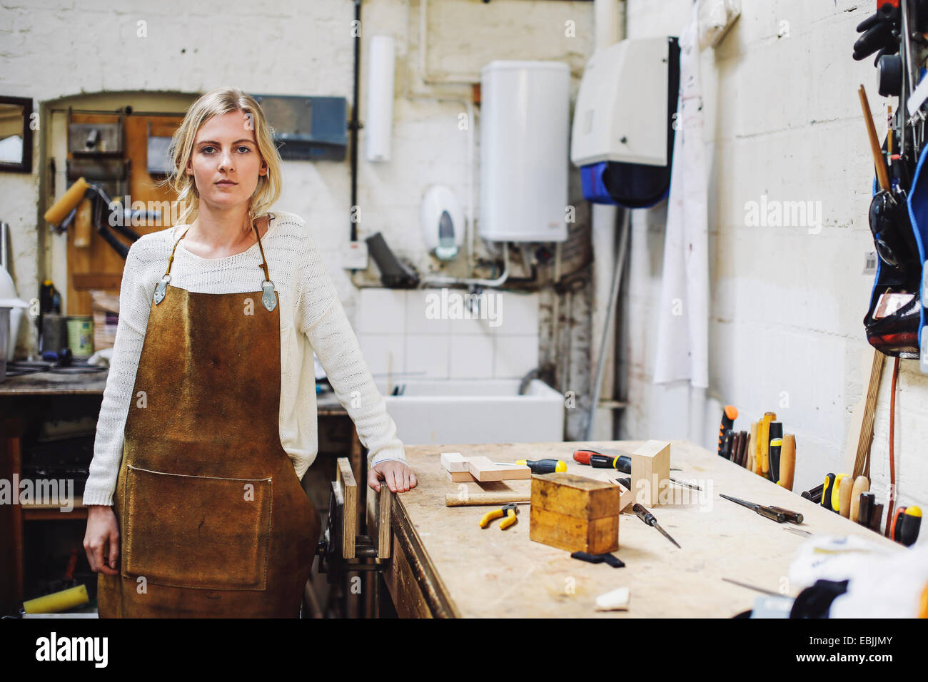 Portrait of young craftswoman leaning on workbench in organ workshop - Stock Image