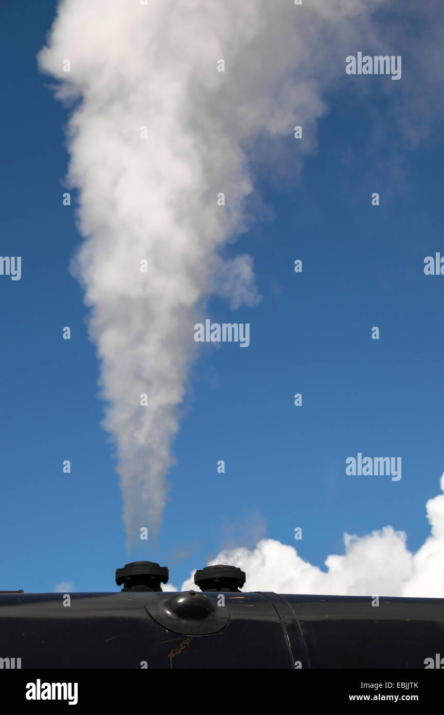 smoke cloud from the funnel of a steam locomotive in front of a blue sky, United Kingdom, Scotland - Stock Image