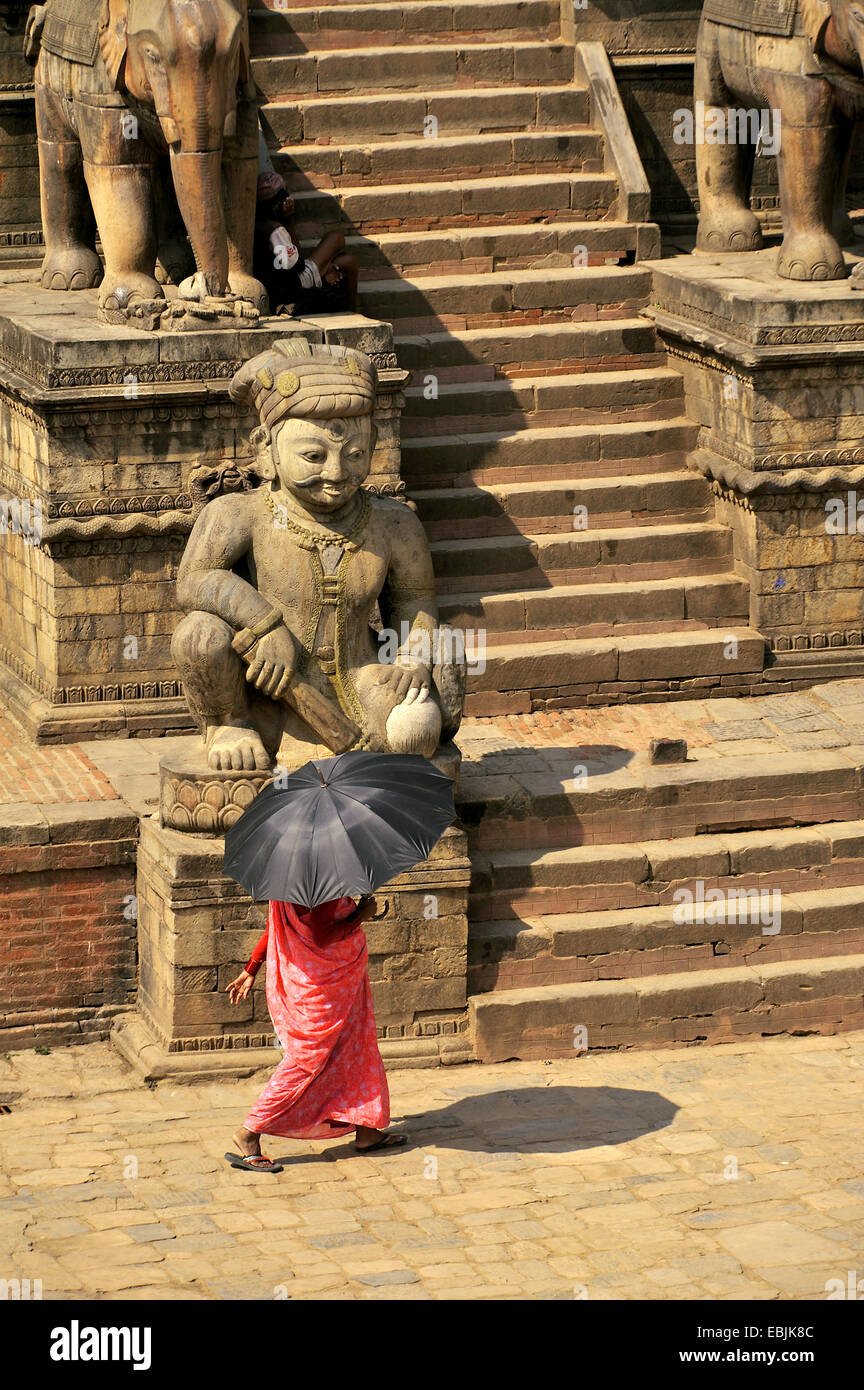 woman with an umbrella serving as a sunshade crossing the Bhaktapur Durbar Square at the royal palace, Nepal, Bhaktapur - Stock Image