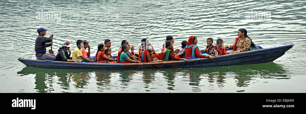 long rowboat full of people on Phewa Lake, Nepal, Pokhara - Stock Image