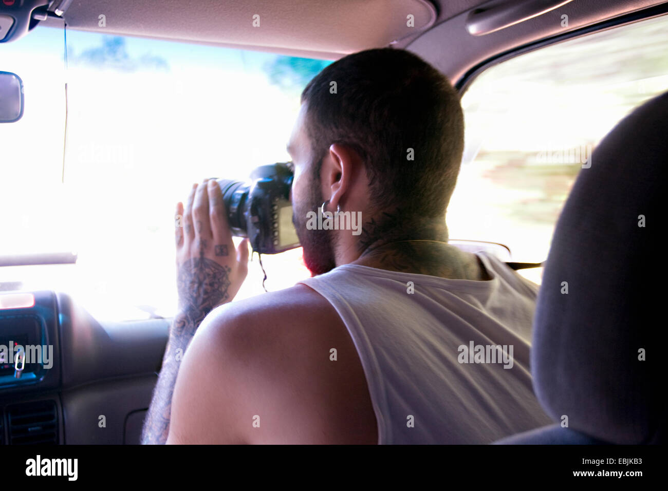 Young man taking photographs through car windscreen - Stock Image