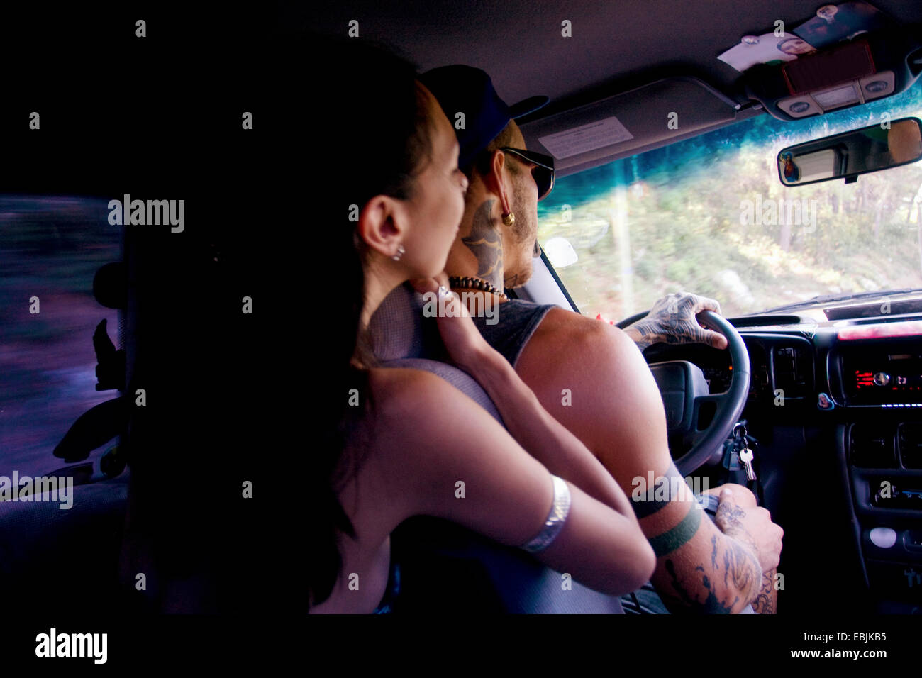 Young couple driving on car road trip - Stock Image