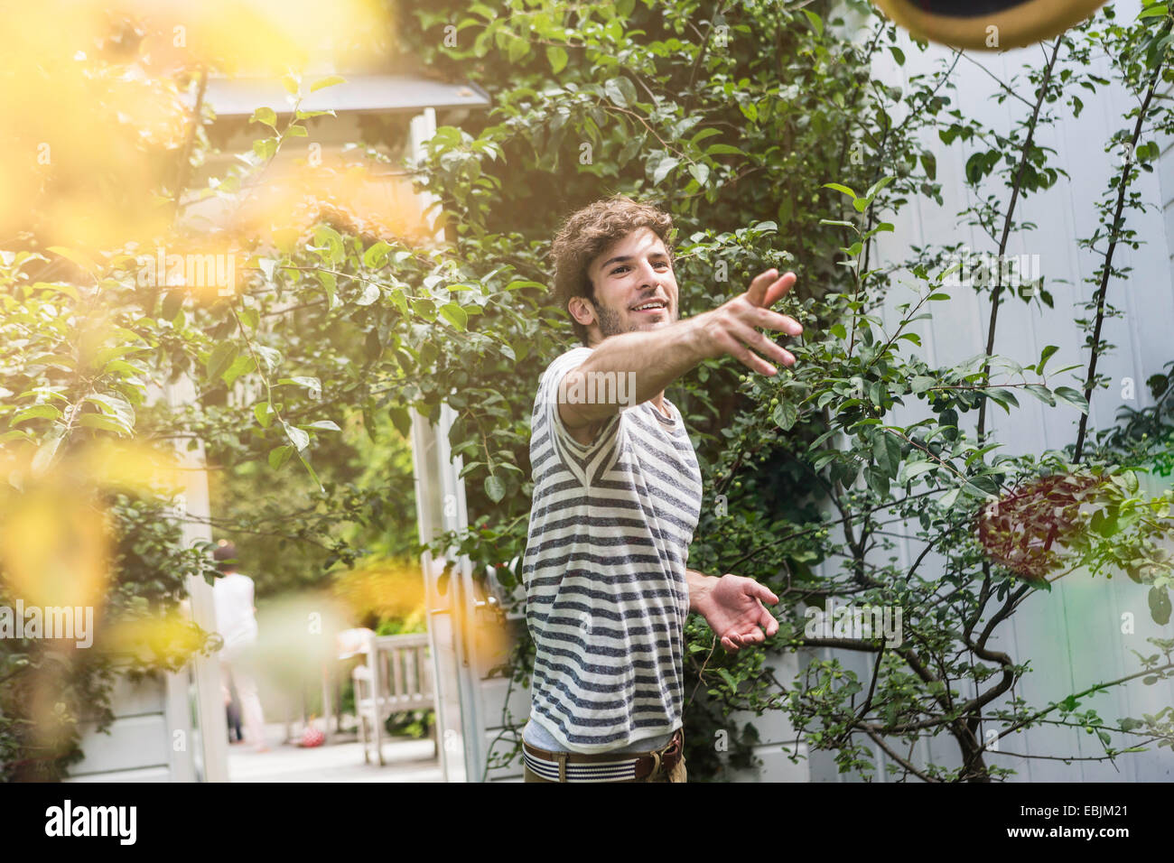 Young man throwing ball in garden - Stock Image