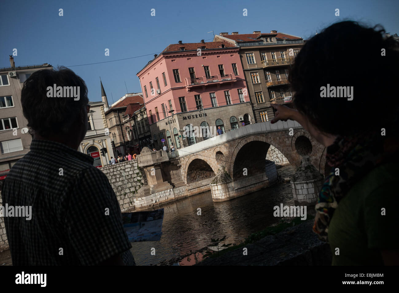 Tourists overlooking Princip bridge and a spot where Gavrilo Princip killed archduke Franz Ferdinand and his wife - Stock Image