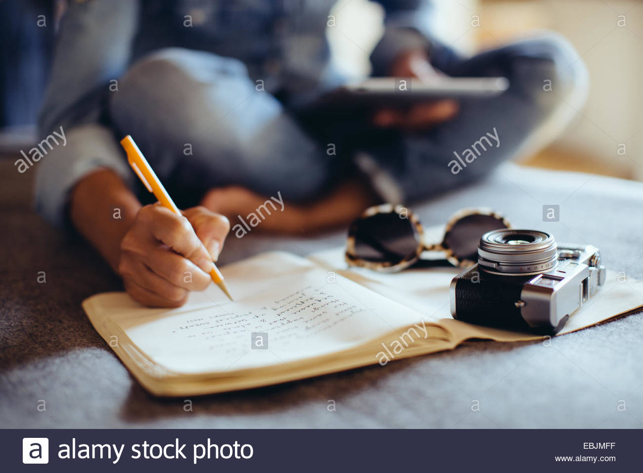 Cropped shot of mid adult woman sitting on bed writing in notebook - Stock Image