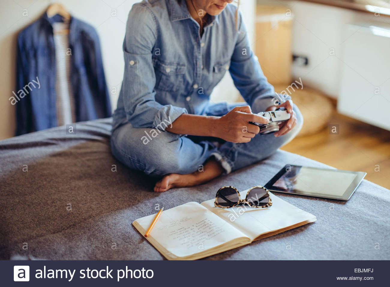 Mid adult woman sitting on bed reviewing photographs on digital SLR camera - Stock Image