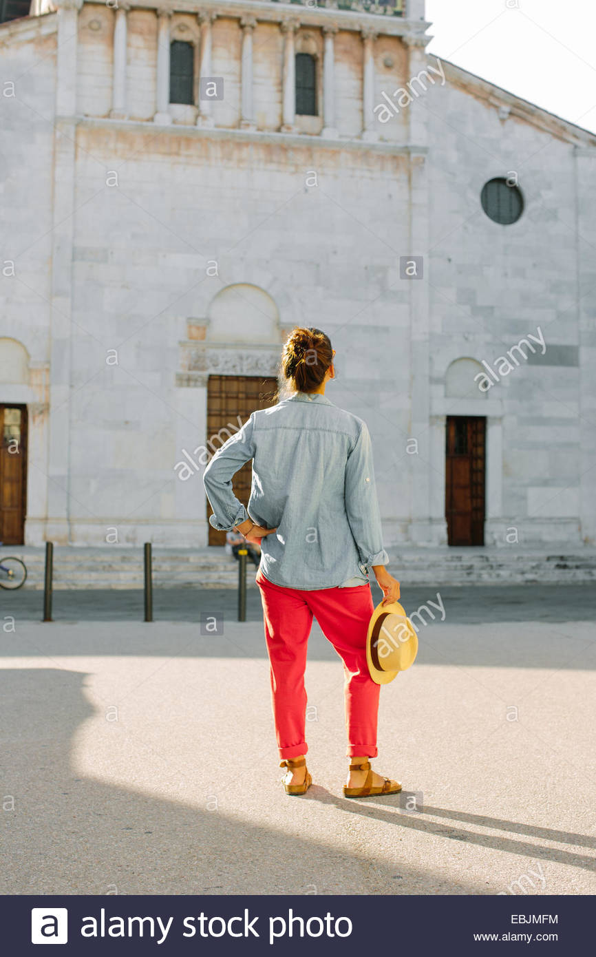 Rear view of mid adult woman looking up at church, Tuscany, Italy - Stock Image