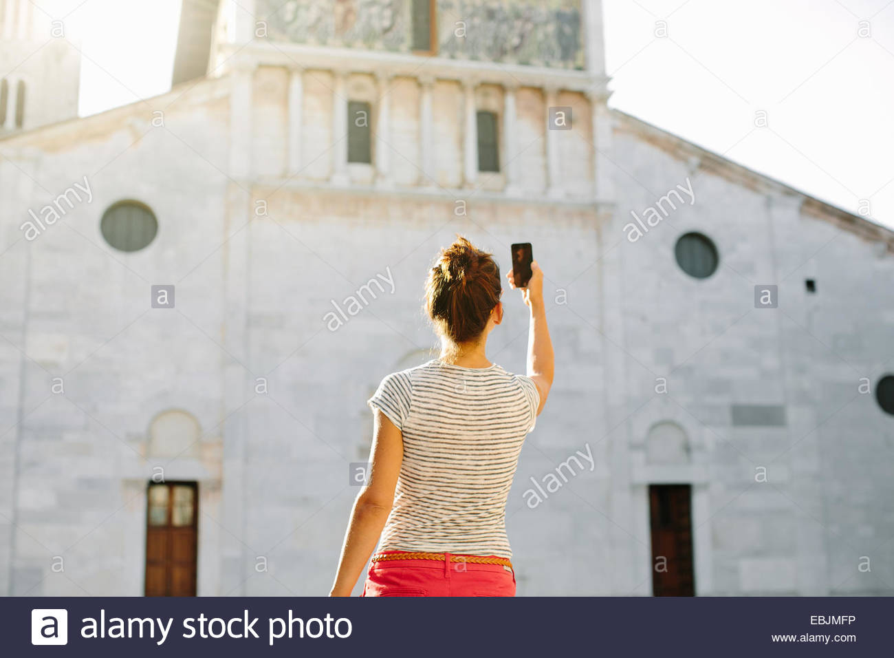 Rear view of mid adult woman photographing church with smartphone, Tuscany, Italy - Stock Image