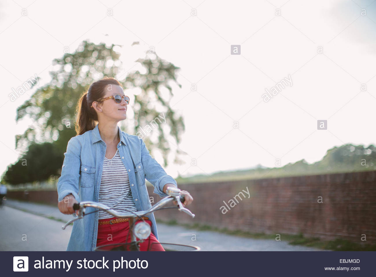 Mid adult woman pushing bicycle on rural road, Tuscany, Italy - Stock Image