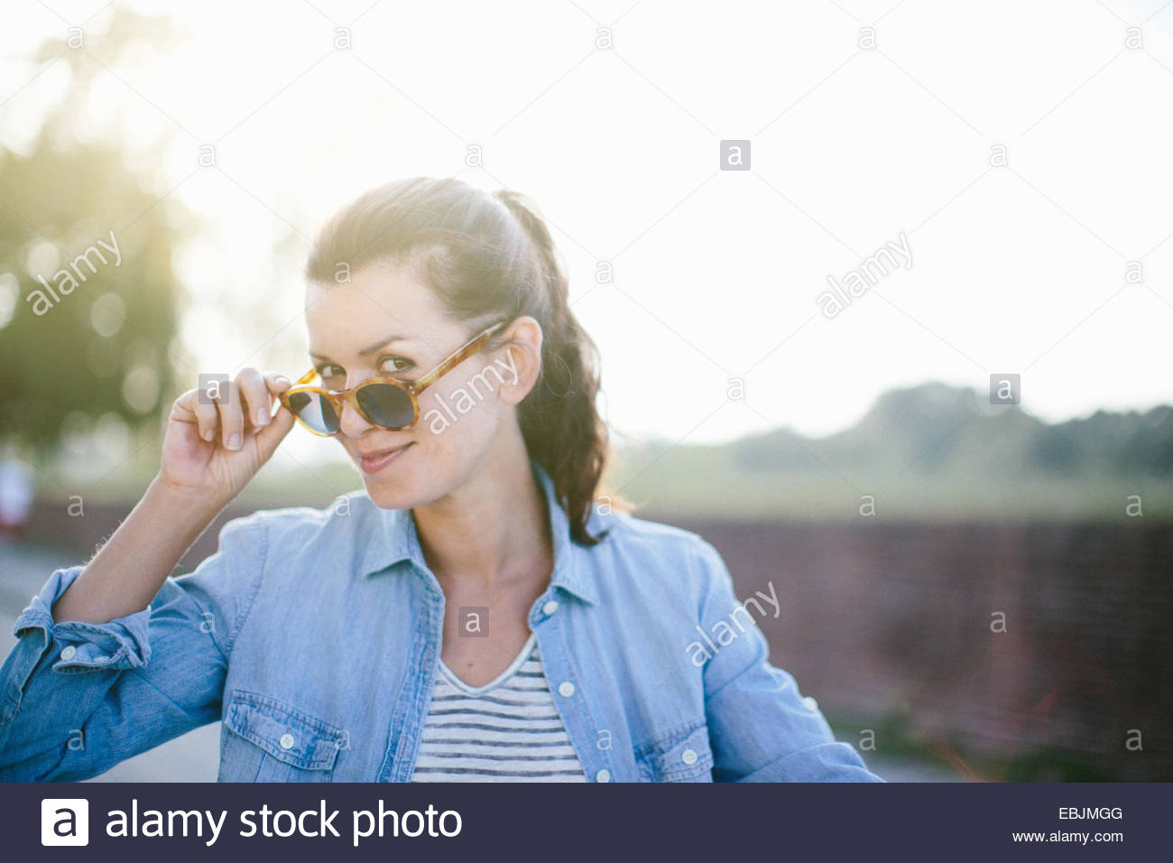 Portrait of mischievous mid adult woman holding sunglasses, Tuscany, Italy - Stock Image