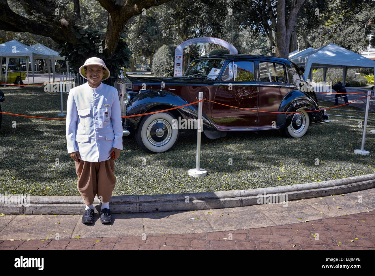 Hotel bell boy against a Rolls Royce Silver Dawn limousine. 1951 Classic British executive motorcar - Stock Image