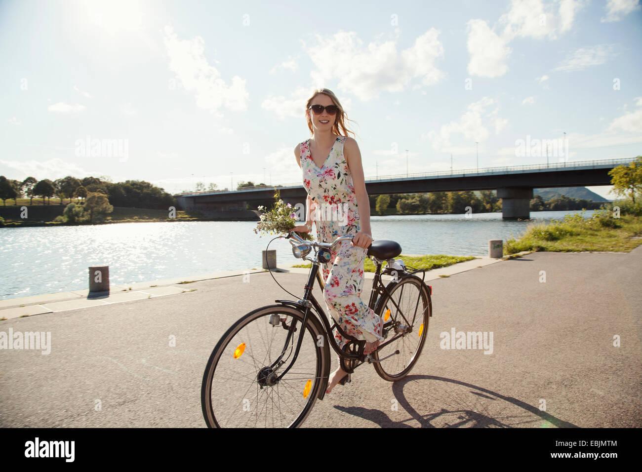 Young woman cycling along riverside, Danube Island, Vienna, Austria Stock Photo