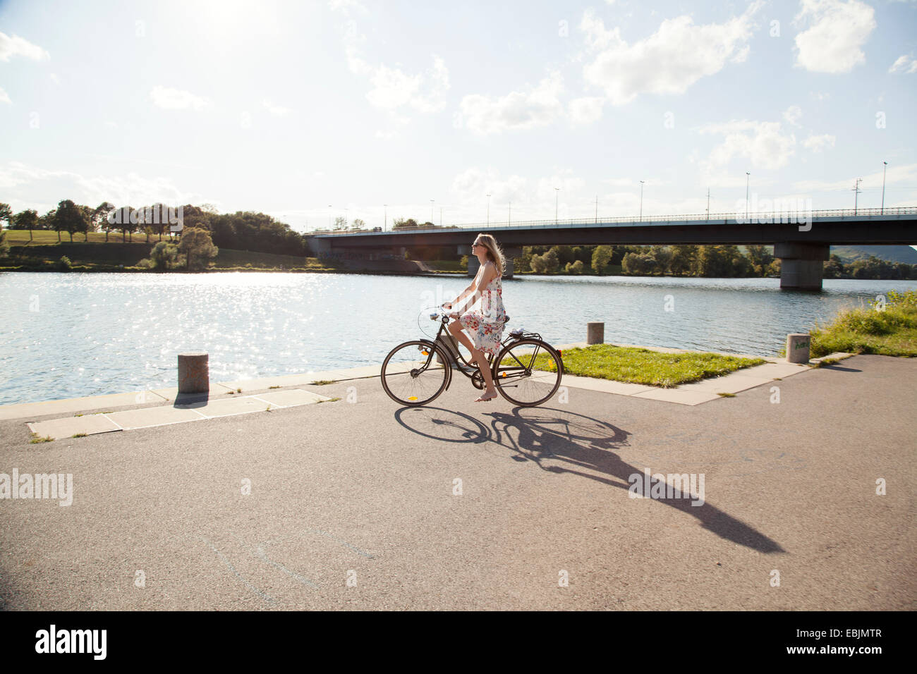 Young woman cycling at riverside, Danube Island, Vienna, Austria - Stock Image
