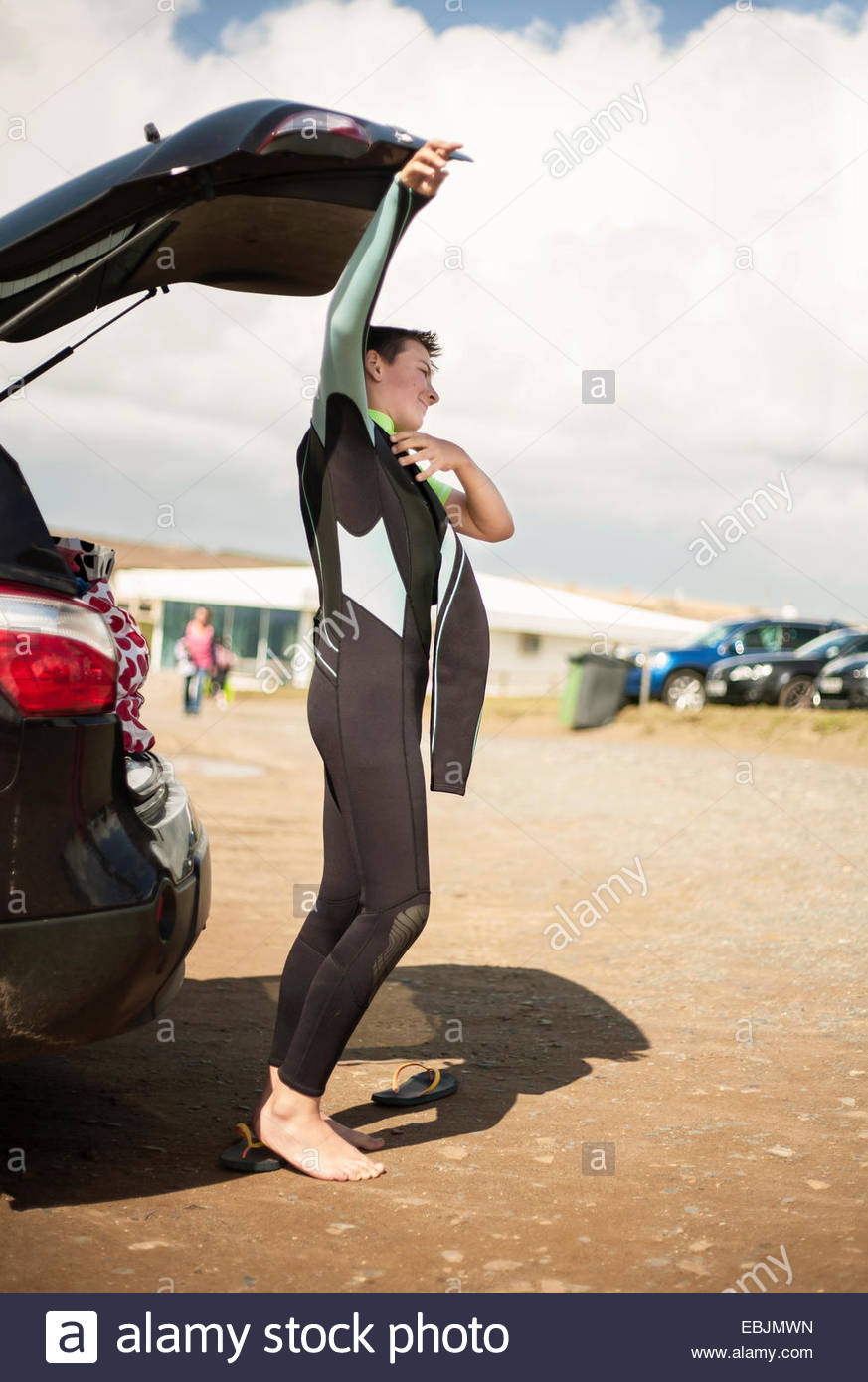 Boy putting on wetsuit by car - Stock Image