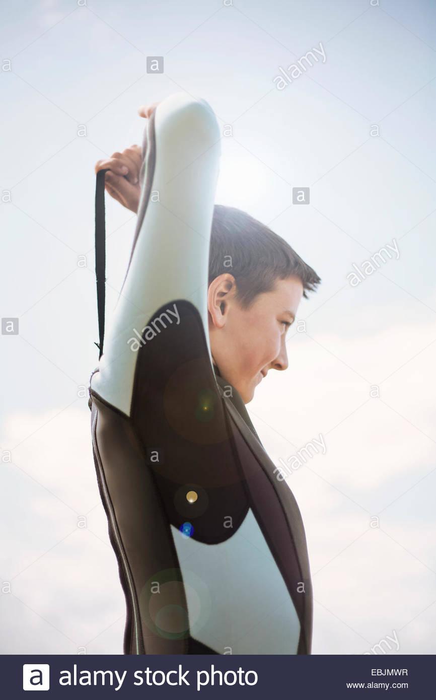 Boy zipping up wetsuit - Stock Image