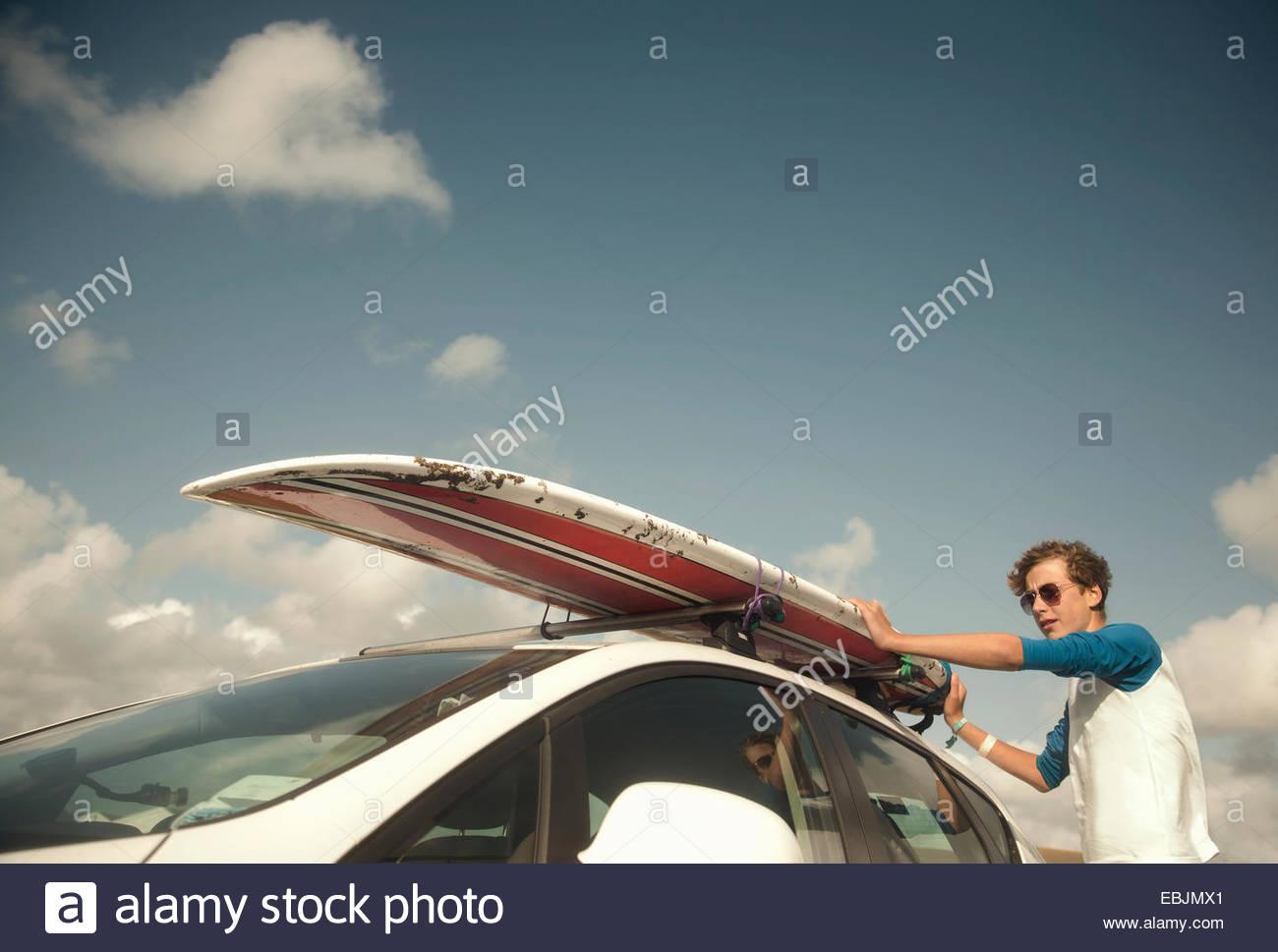 Teenage boy putting surfboard on top of car - Stock Image