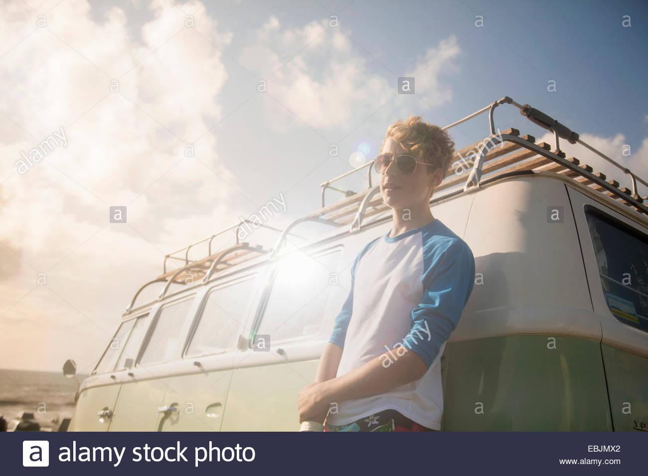Teenage boy leaning against vehicle - Stock Image