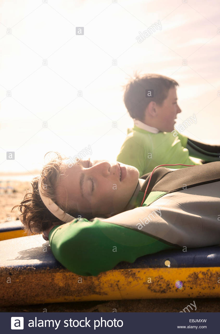 Teenage boy lying asleep on surfboard - Stock Image