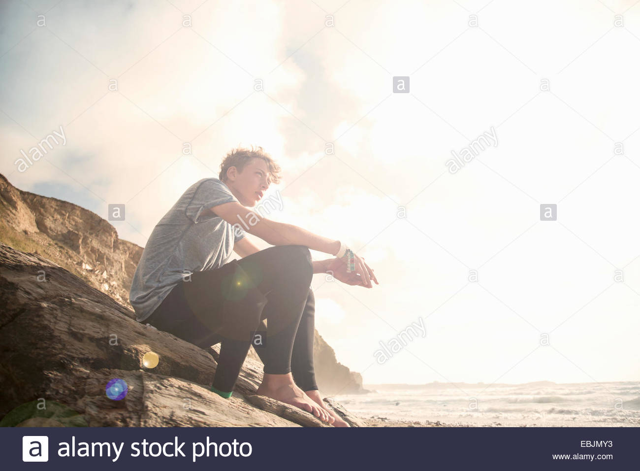 Teenage boy sitting on rocks - Stock Image