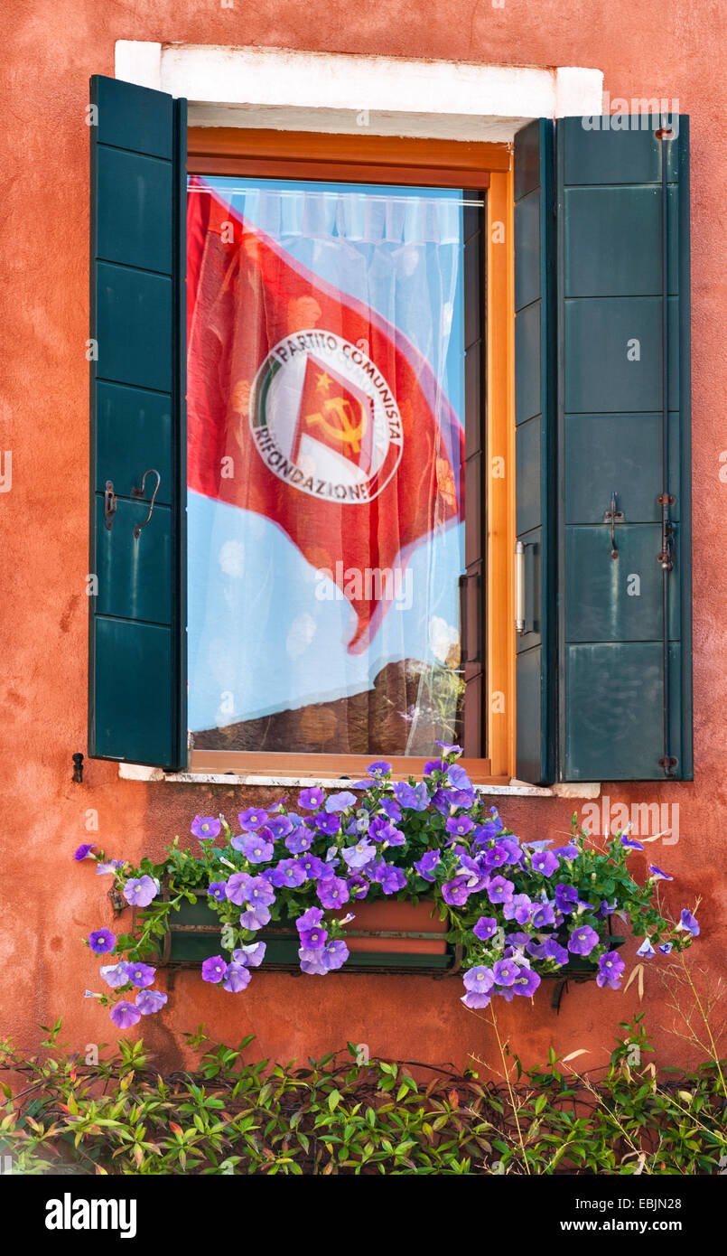 Venice, Italy. An Italian Communist Party (PRC) flag flying on May Day (International Workers' Day), reflected - Stock Image