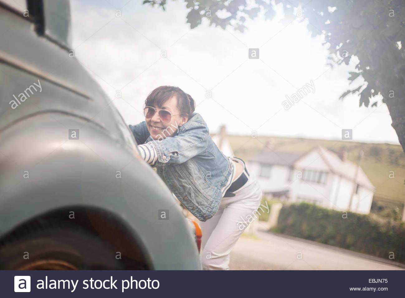 Woman pushing broken down car Stock Photo