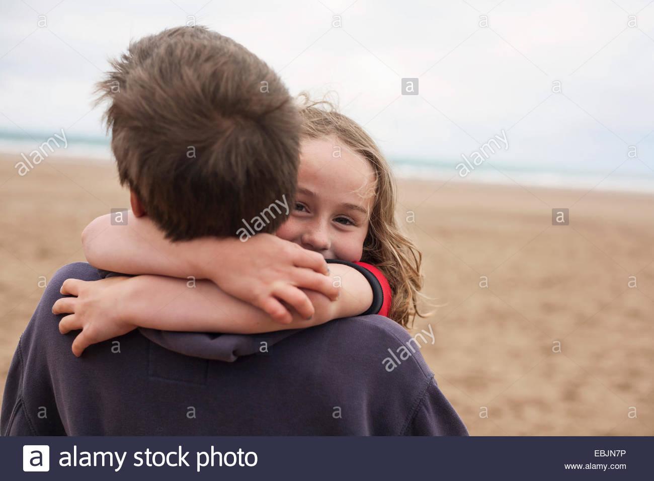 Girl hugging boy at beach - Stock Image