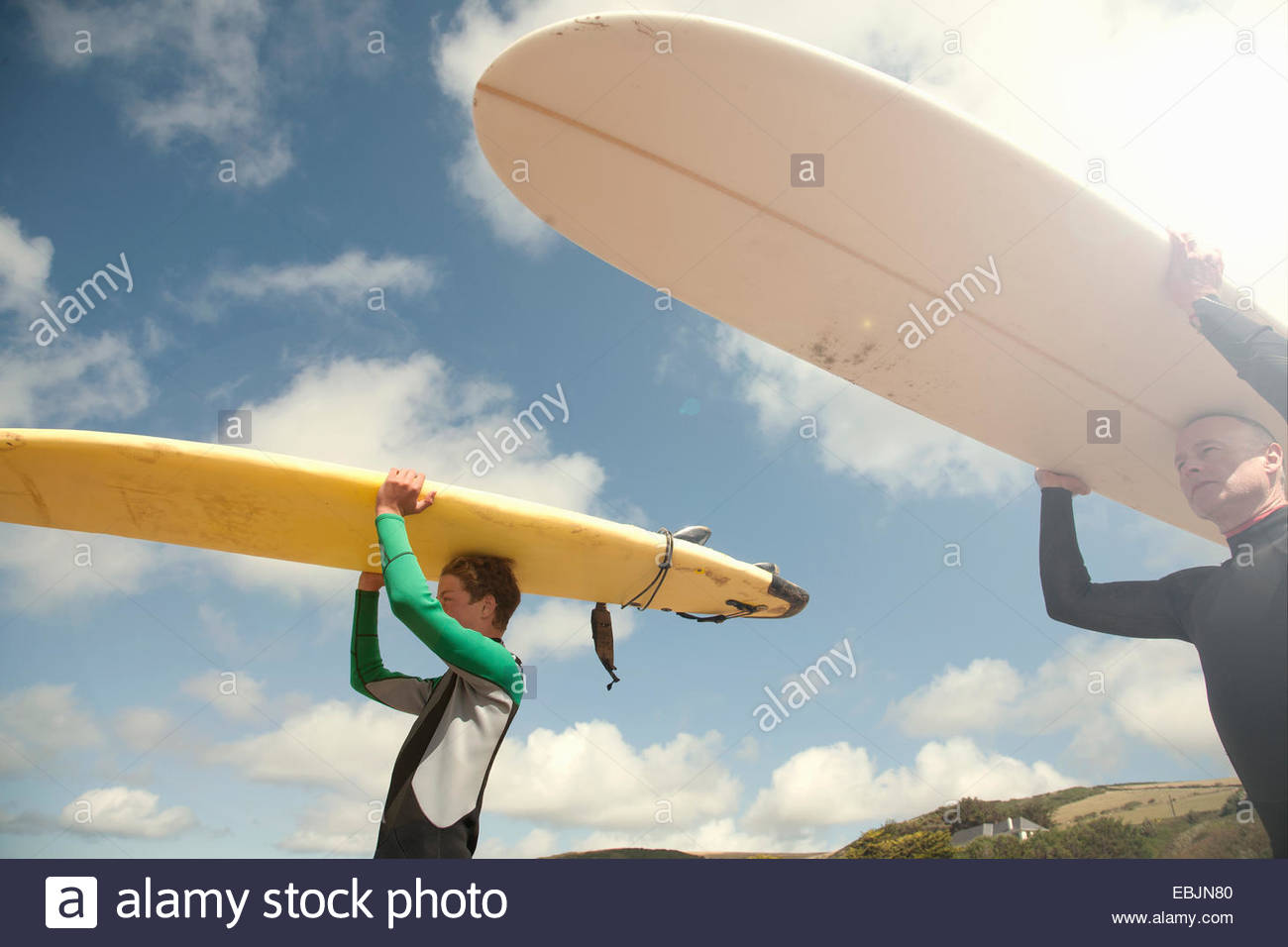 Man and teenage boy carrying surfboards - Stock Image