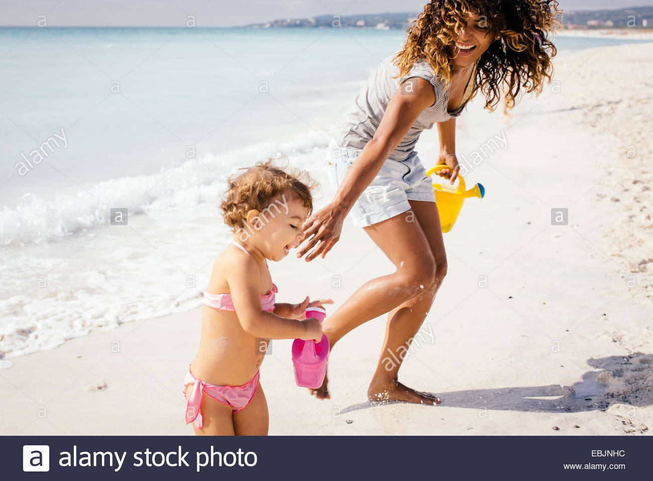 Mother and toddler daughter with toy watering cans on beach, Tuscany, Italy - Stock Image