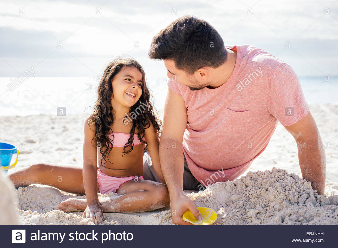 Girl and father building sandcastle on beach, Tuscany, Italy - Stock Image