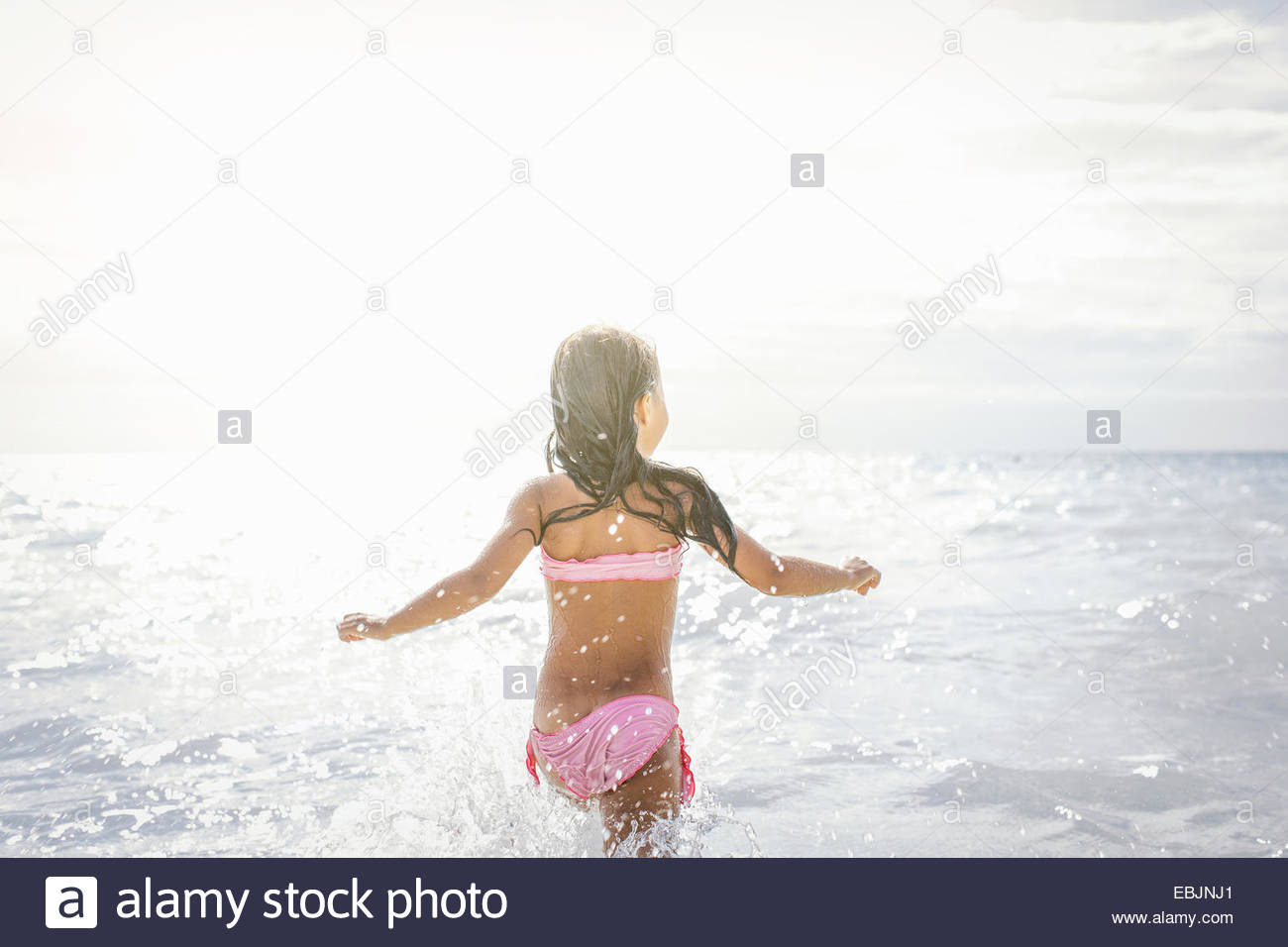 Rear view of girl running and splashing in sea, Tuscany, Italy - Stock Image