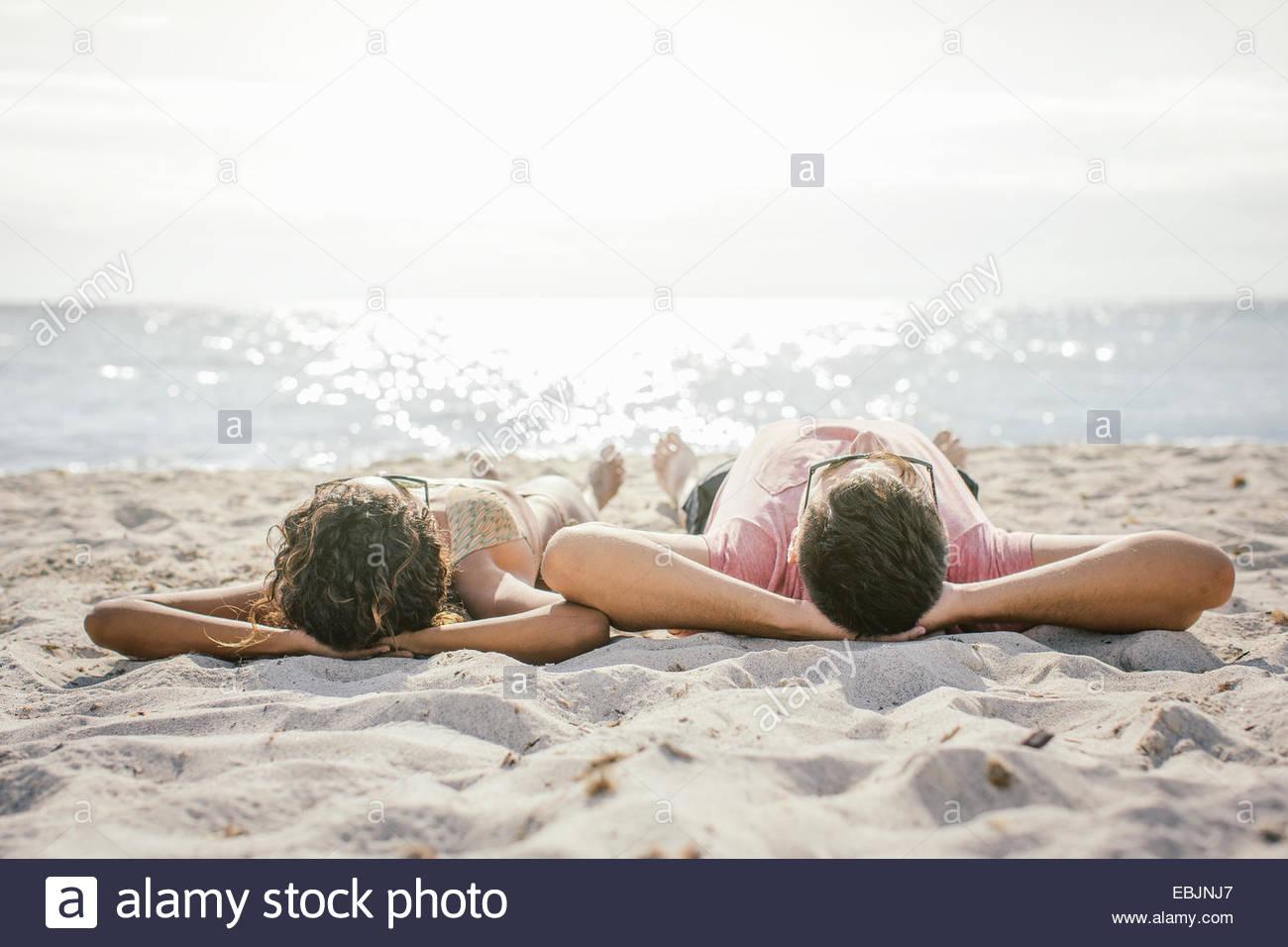 Couple lying on beach sunbathing, Tuscany, Italy - Stock Image