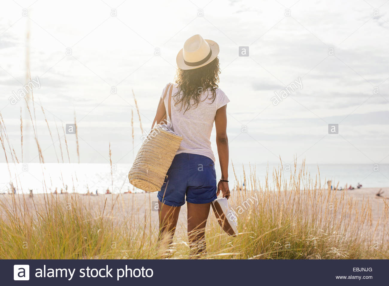 Rear view of young woman with beach bag in dunes, Tuscany, Italy - Stock Image