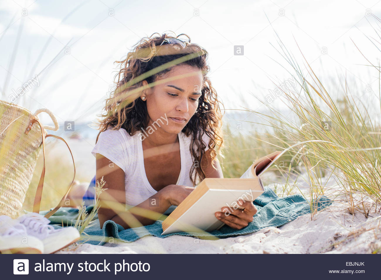 Young woman cross reading a book in beach dunes, Tuscany, Italy - Stock Image