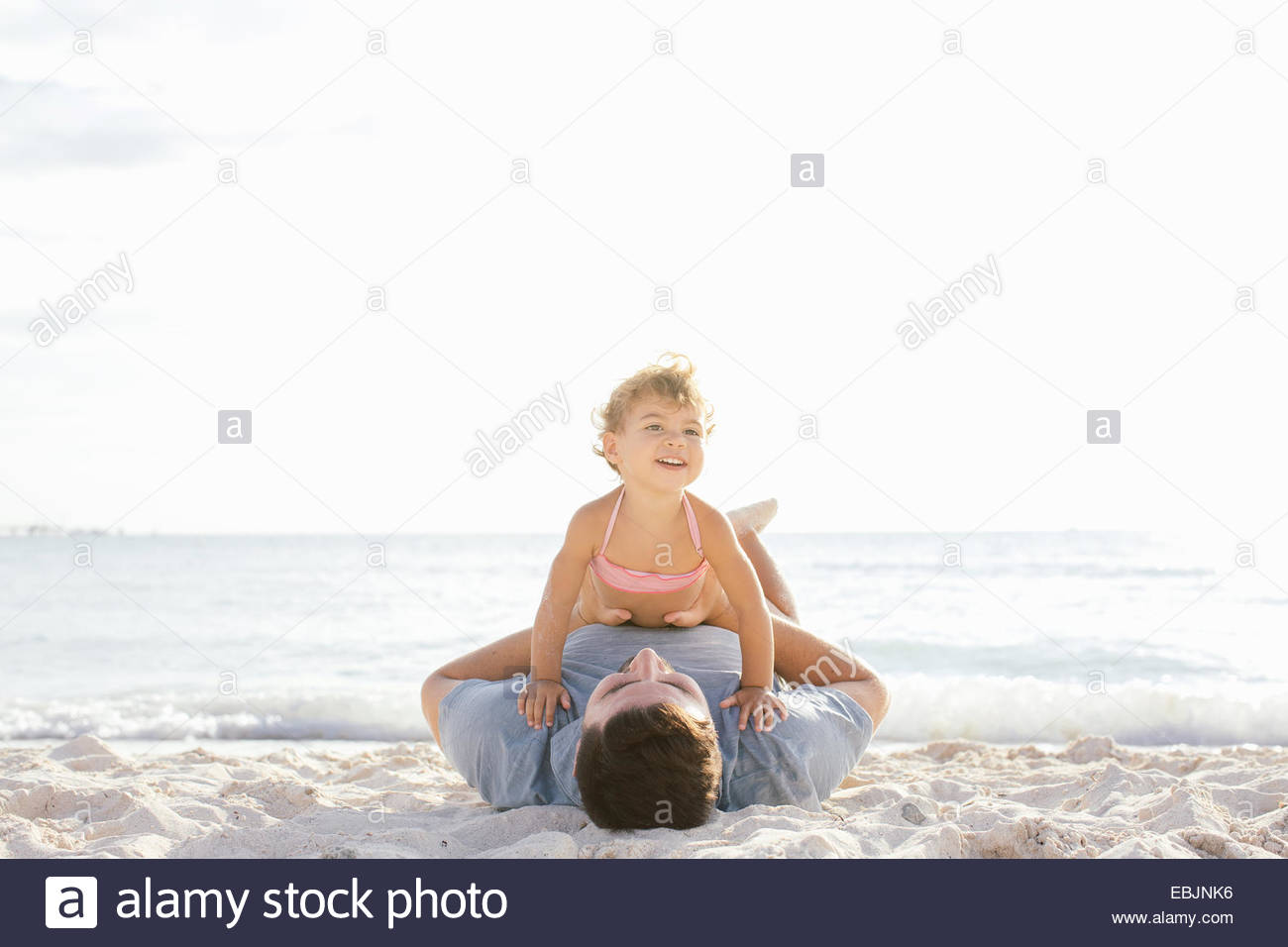 Female toddler sitting on top of father at beach, Tuscany, Italy - Stock Image