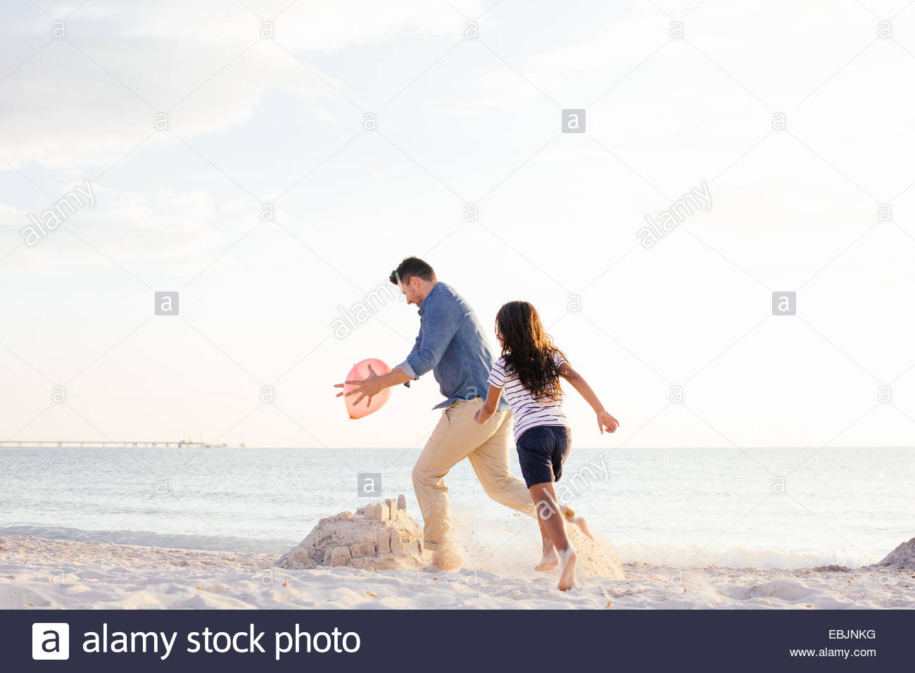 Girl chasing father for balloon on beach, Tuscany, Italy - Stock Image
