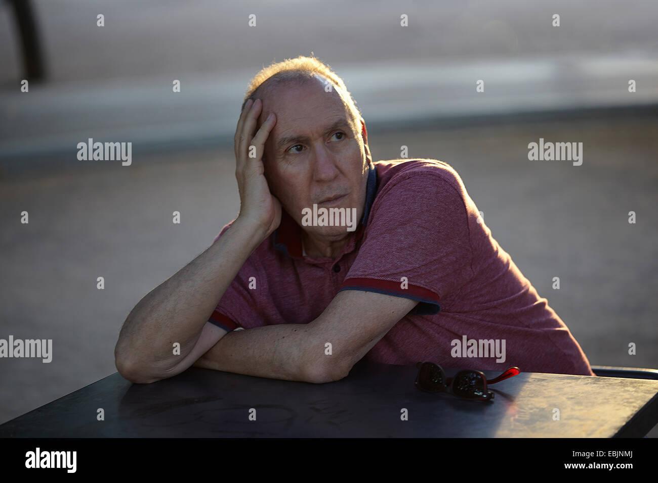 Senior man sitting at table, resting on elbow - Stock Image