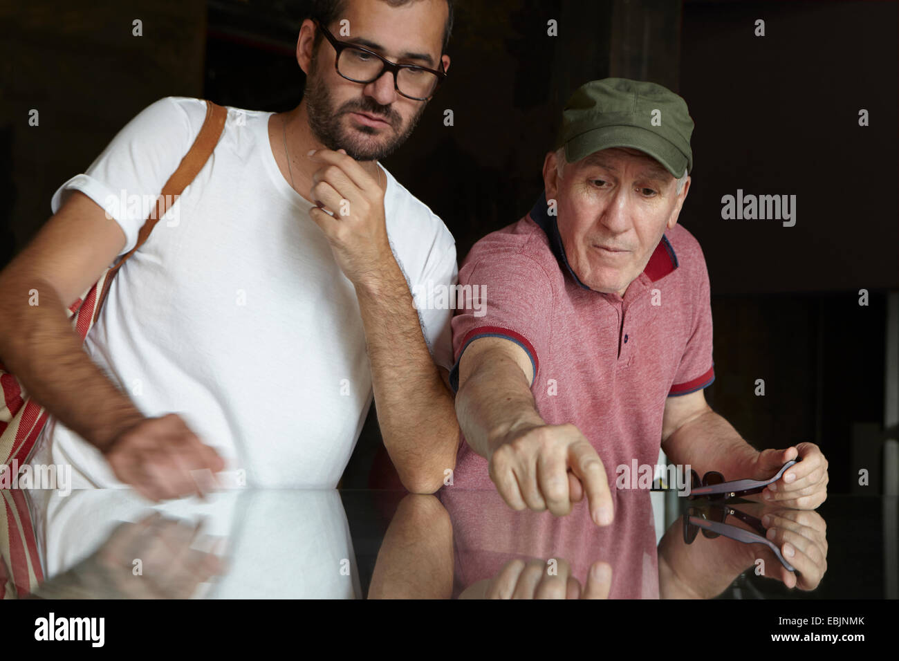 Mid adult man looking at senior man pointing - Stock Image