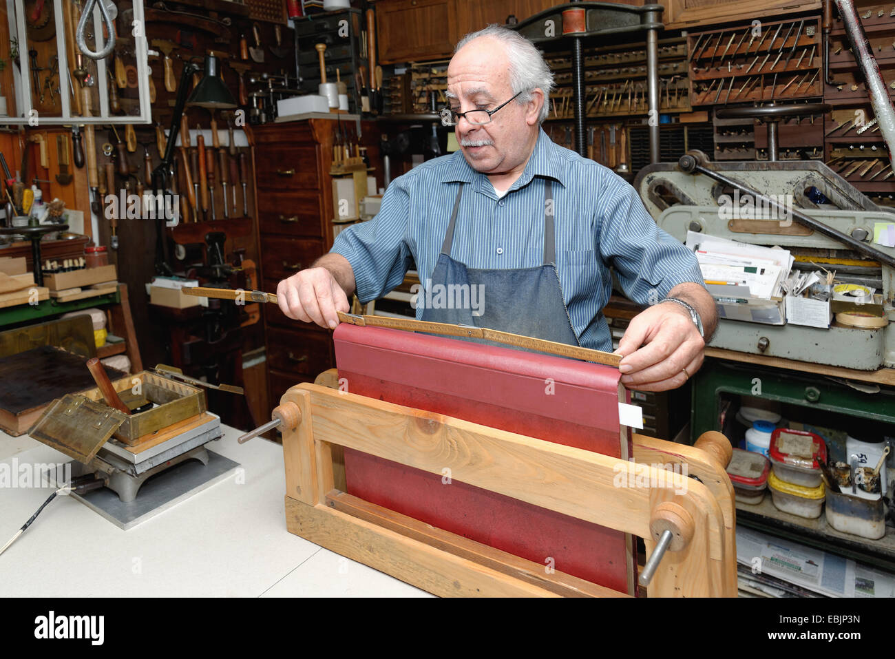 Senior man measuring book spine in traditional bookbinding workshop - Stock Image
