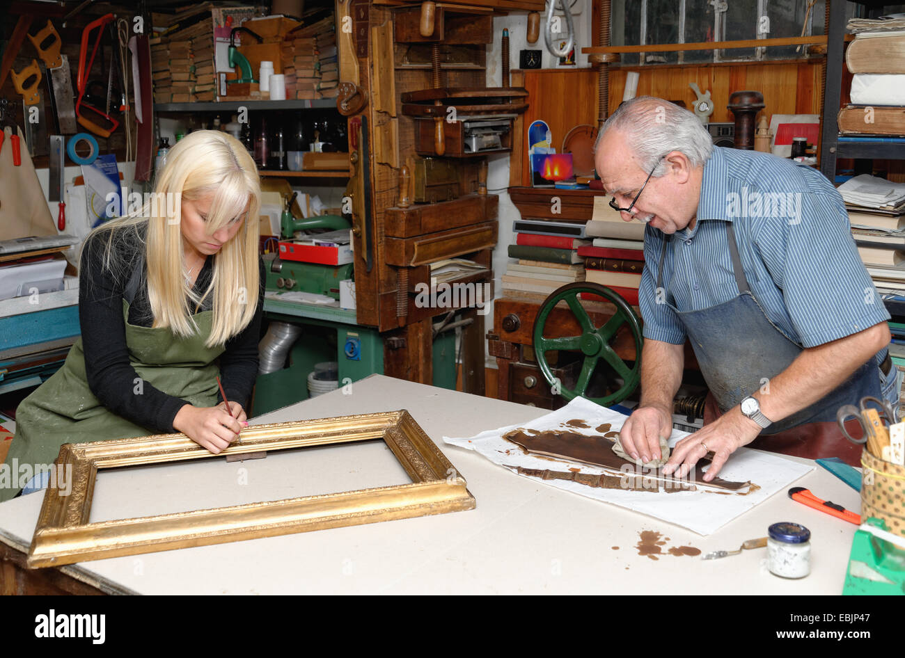 Senior man and young woman restoring picture frame and book spine in traditional bookbinding workshop - Stock Image