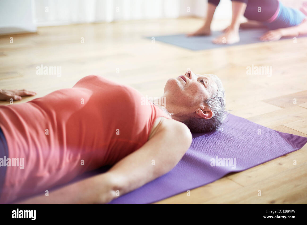 Mature woman lying on back in pilates class Stock Photo