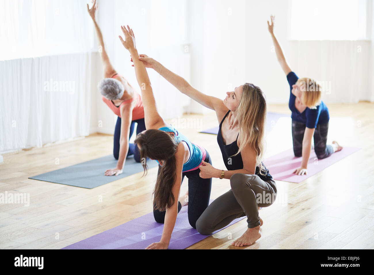 Women kneeling and raising arms in pilates class - Stock Image