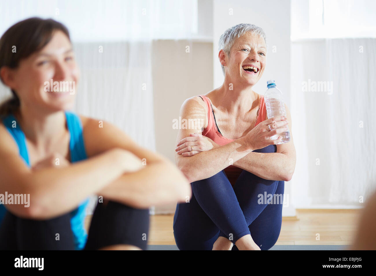 Two women taking a break in pilates class - Stock Image