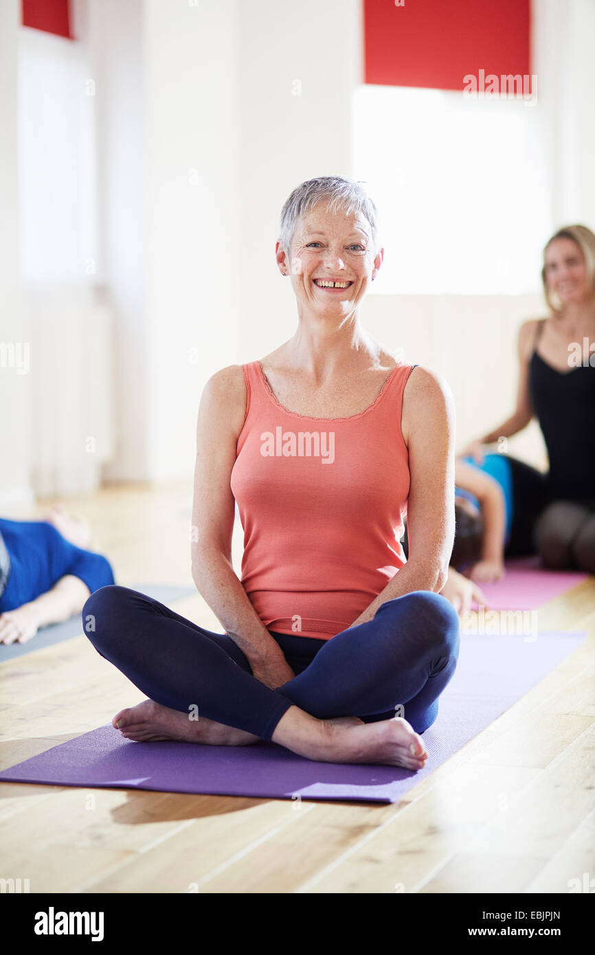 Portrait of mature woman sitting cross legged in pilates class - Stock Image