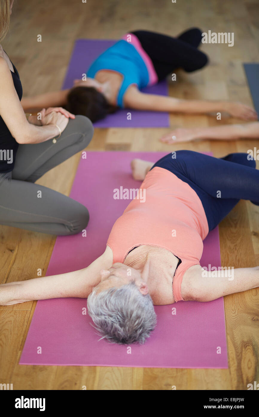 Female students lying on back and twisting hips in pilates class - Stock Image