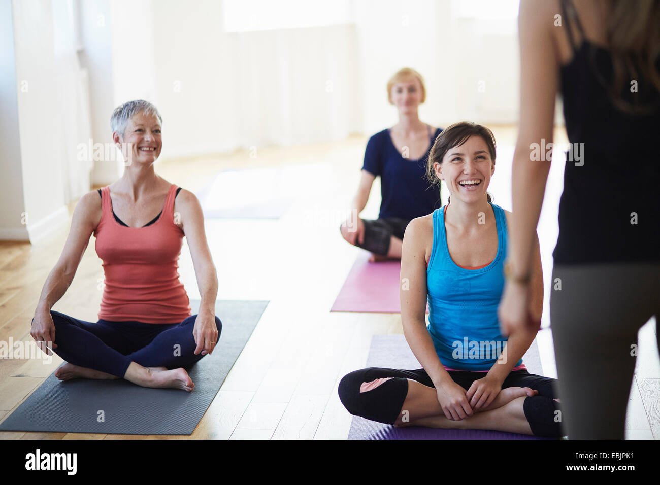 Female students watching and listening to tutor in pilates class - Stock Image