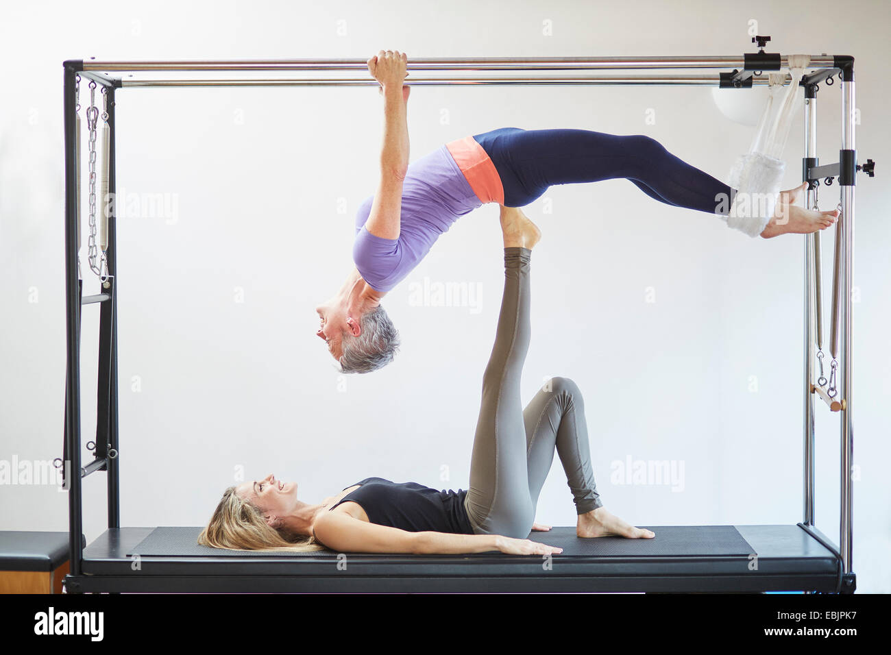 Two mature women practicing pilates on trapeze table in pilates gym - Stock Image