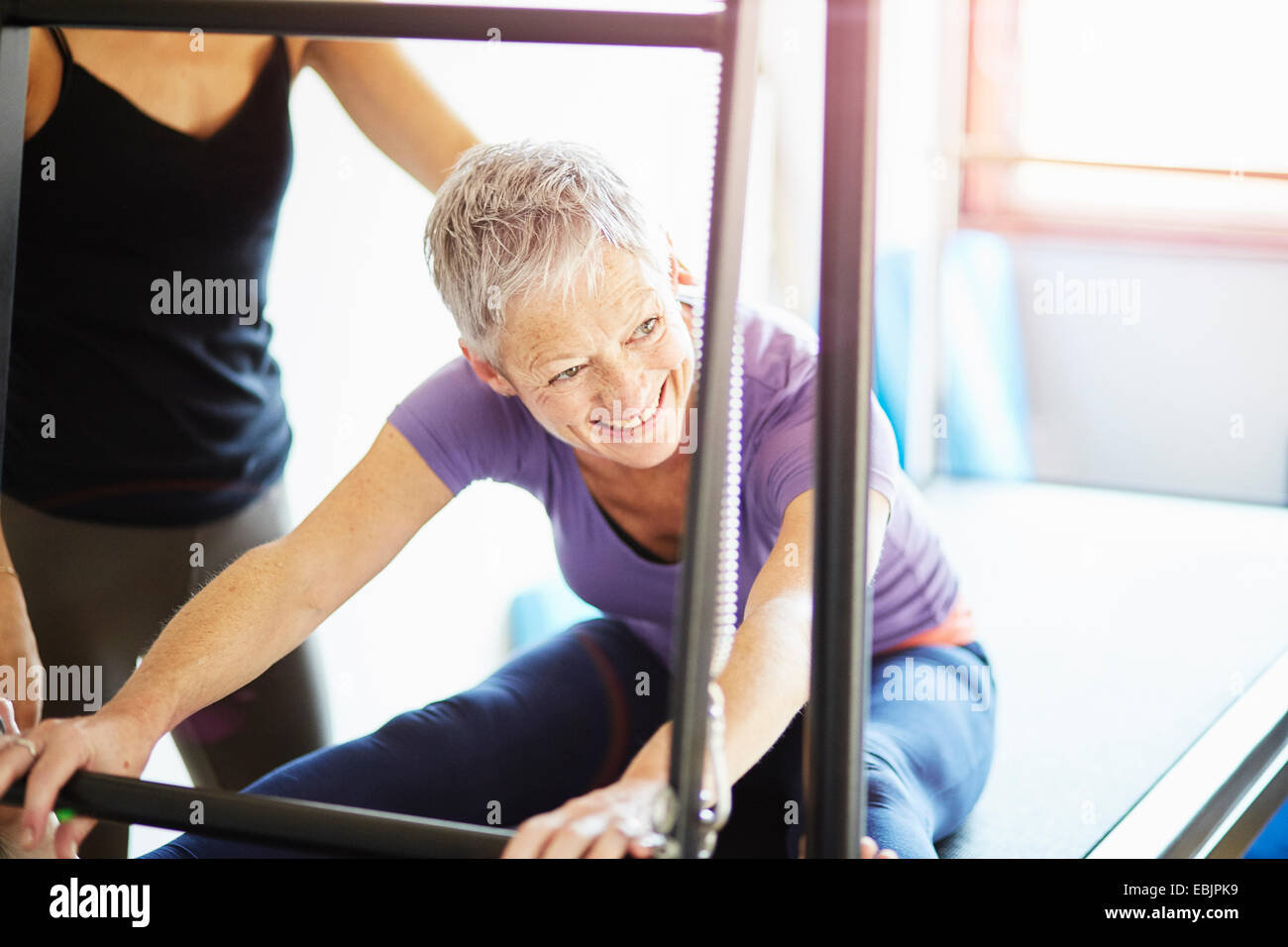Mature woman and tutor practicing pilates on trapeze table in pilates gym - Stock Image