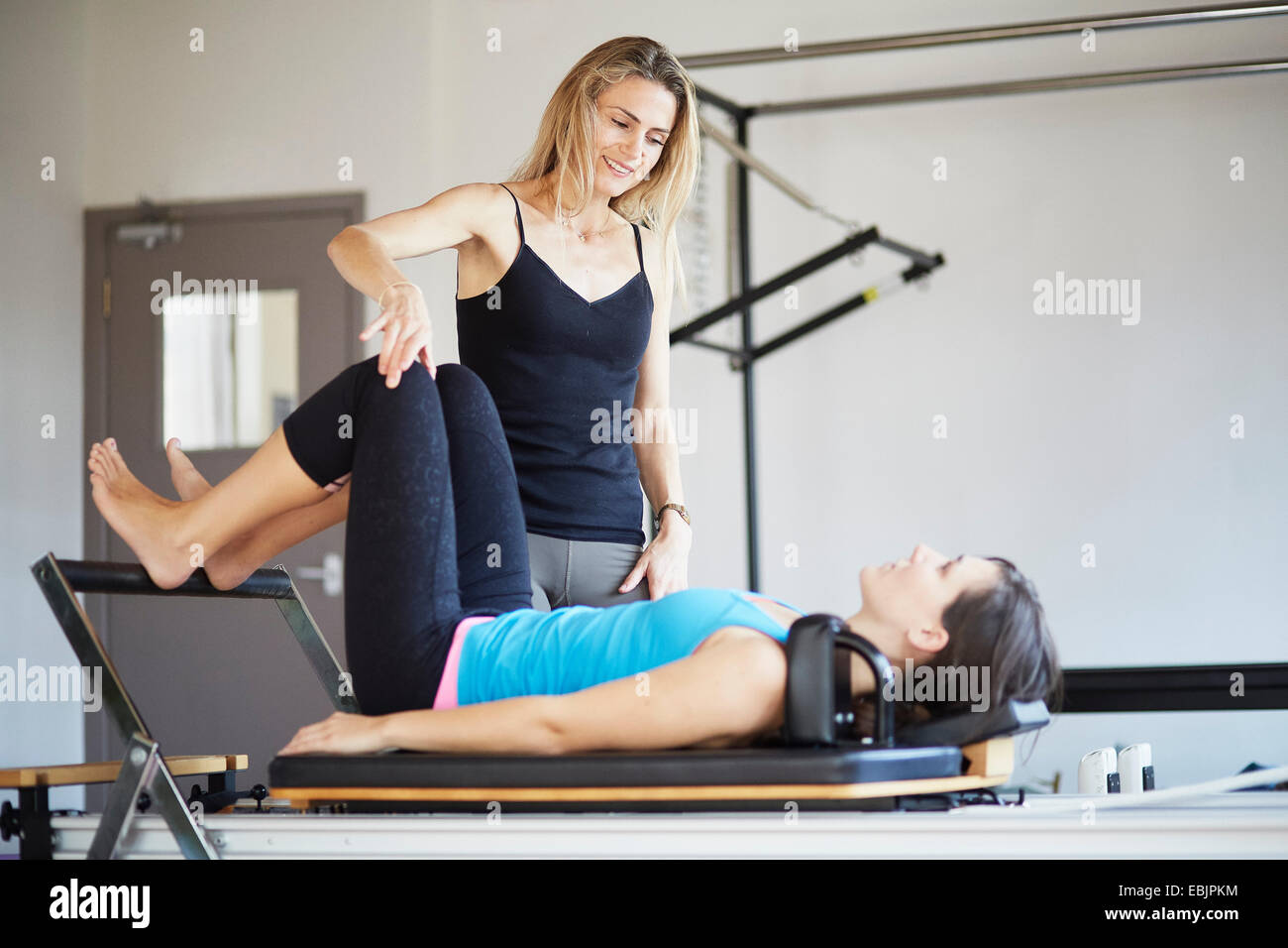 Female student lying on reformer in pilates gym - Stock Image