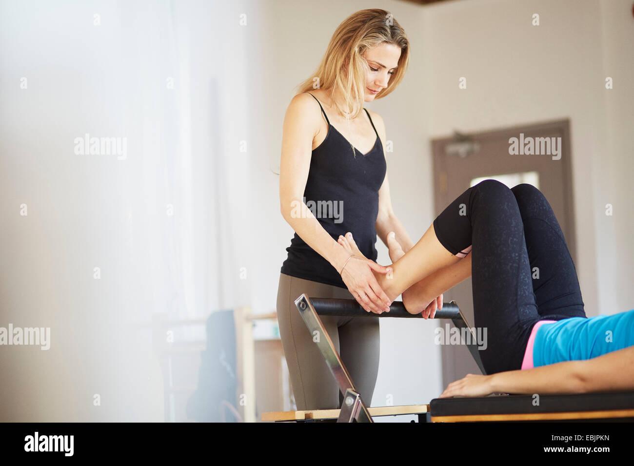 Tutor holding feet of female student lying on reformer in pilates gym - Stock Image